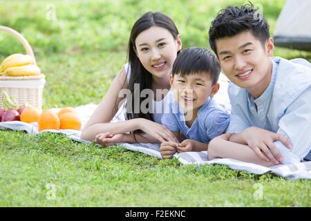Felice famiglia giovane avente picnic sull'erba Foto Stock