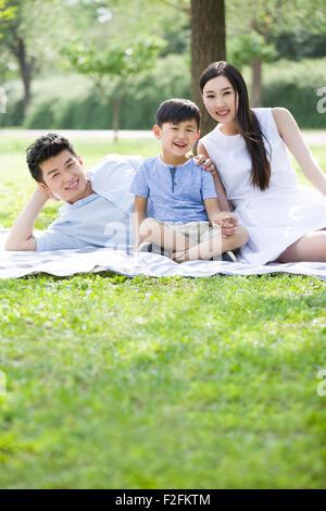 Felice famiglia giovane seduto sull'erba Foto Stock