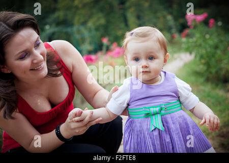 Imparare a camminare - madre aiutare la sua piccola figlia Foto Stock