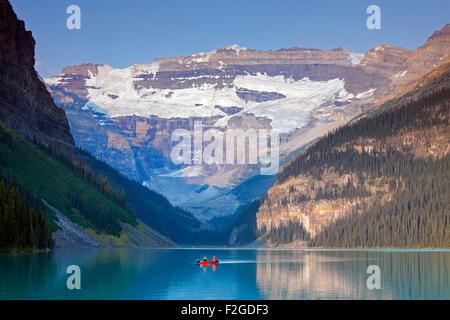 I turisti in rosso in canoa sul lago glaciale di Louise con Ghiacciaio Victoria, il Parco Nazionale di Banff, Alberta, Foto Stock