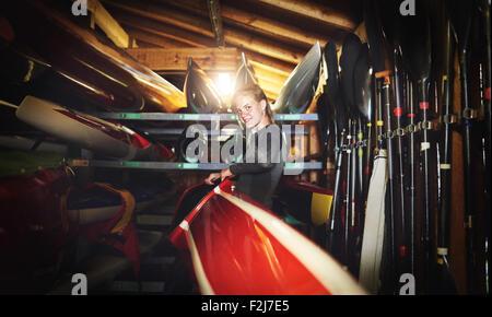 Elite rower ottenere pronto controllando il suo kayak Foto Stock