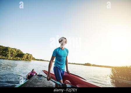 Giovane uomo che porta un kayak dopo arrivare fuori dall'acqua Foto Stock