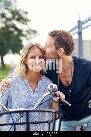 Affettuosa giovane baciare la sua ragazza sulla fronte come essi godono di un giorno di estate in aria fresca sui Foto Stock
