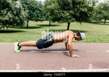 Atletica Giovane uomo che fa pushups nel parco Foto Stock