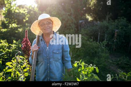 Attraente sorridente contadino nel cappello di paglia utilizzando tablet in  stabile  Ritratto di sorridere senior donna con cappello di paglia nel suo  ... 900a40f05f01