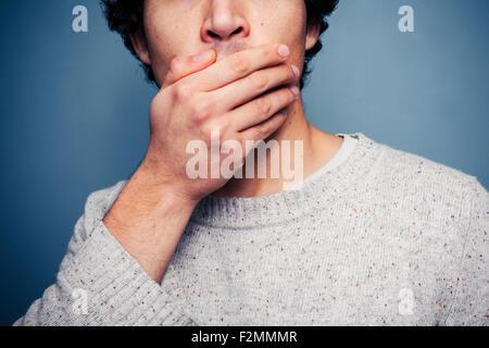 Giovane uomo che copre la bocca in stato di shock Foto Stock