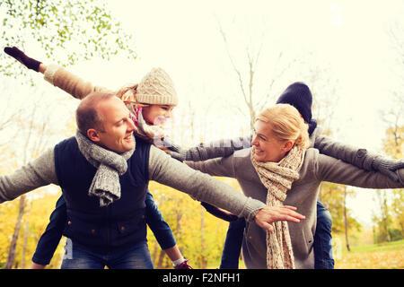 La famiglia felice avendo divertimento nel parco di autunno Foto Stock