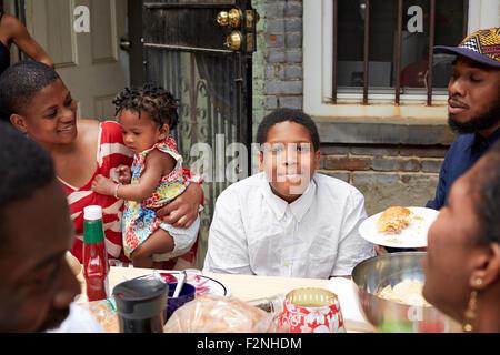 Famiglia mangiare insieme al barbecue nel cortile Foto Stock