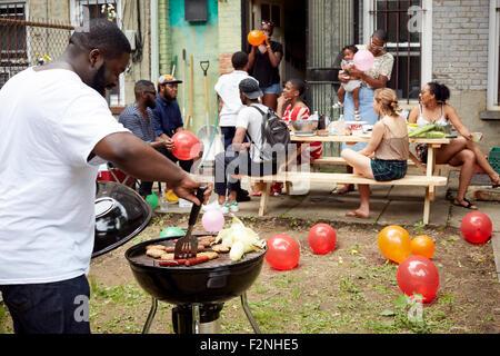 Gli amici sorseggiando backyard barbecue Foto Stock