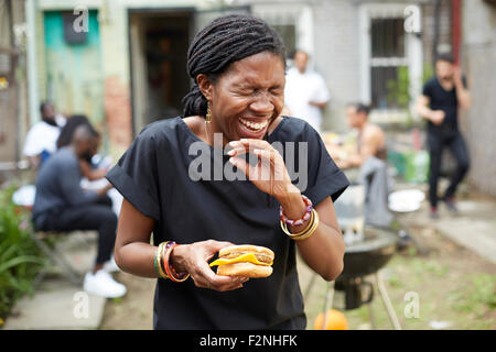African American donna di mangiare al barbecue nel cortile Foto Stock