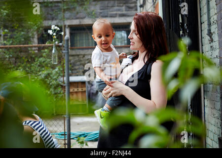 Donna che mantiene il bambino figlio nel cortile posteriore Foto Stock