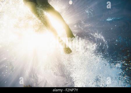 Ragazza caucasica nuoto sott'acqua in piscina Foto Stock