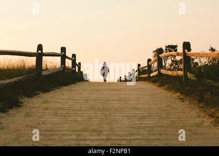 Silhouette di donna che cammina sulla passerella in legno Foto Stock