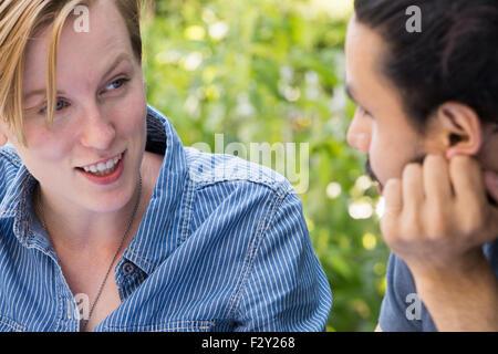 Close up di un giovane uomo e donna seduta a fianco a fianco, sorridente e parlare. Foto Stock