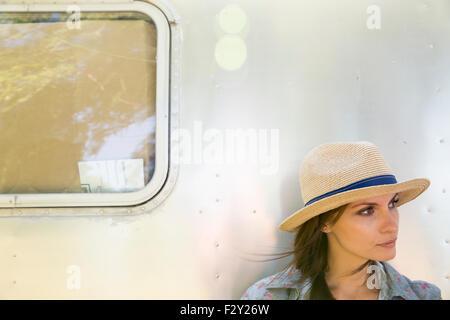 Una giovane donna che indossa un cappello seduti all'ombra di un color argento di rimorchio. Foto Stock