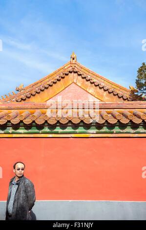 Turisti cinesi si erge di fronte a un dipinto di rosso parete in corrispondenza della Città Proibita di Pechino Foto Stock
