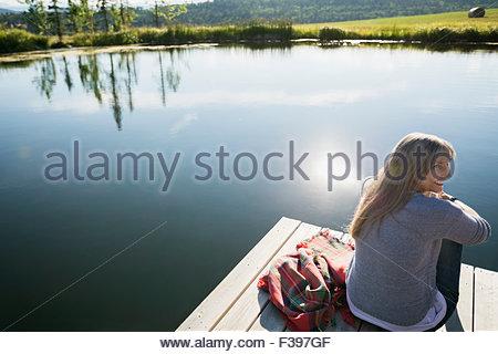 Donna sorridente rilassante sul dock a sunny lakeside Foto Stock