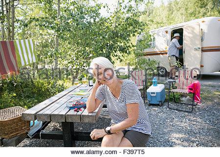 Ritratto sorridente donna senior al campeggio Tavolo picnic Foto Stock