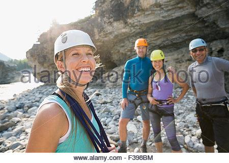 Sorridente amici in arrampicata caschi Foto Stock