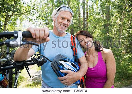 Ritratto di Coppia sorridente con la mountain bike Foto Stock
