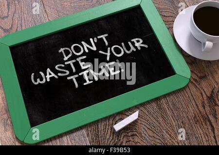 Non sprecare il tuo tempo - Preventivo motivazionale disegnati a mano sulla lavagna verde su un tavolo di legno. Foto Stock