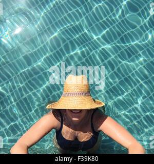 Donna in piedi in piscina guardando in alto Foto Stock