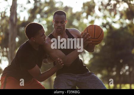 Due giovani uomini giocare a basket nel parco al tramonto Foto Stock