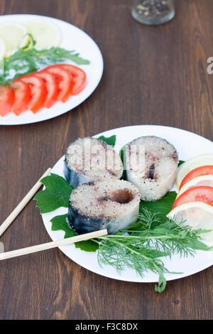 Pezzi di sgombri freschi di spezie con verdure sulla piastra bianca Foto Stock