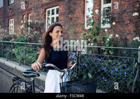 Ritratto di giovane e bella donna che cammina lungo la strada con una bicicletta. Donna con moto passeggiando per Foto Stock