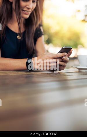 Immagine ritagliata della giovane donna utilizzando smart phone in un outdoor cafe. Femmina di lettura di un messaggio di testo sul suo telefono cellulare.