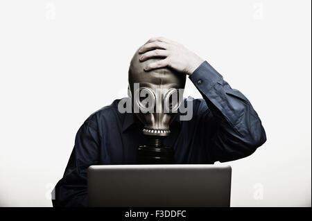 Studio shot dell uomo nella parte anteriore del computer portatile indossando maschera a gas Foto Stock