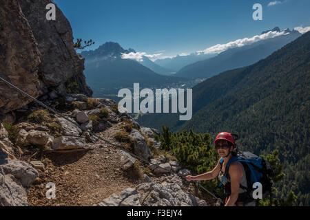 Scalatore femmina persona quasi una battuta sul Ettore Bovero via ferrata con vedute di Cortina (Dolomiti, Italia) Foto Stock
