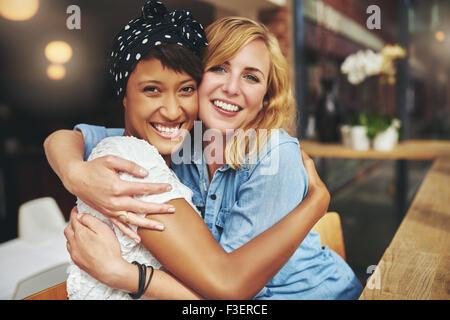 Due lieti affettuosa giovane donna che abbraccia ogni altra in un abbraccio mentre ridono e sorridente, giovane Foto Stock