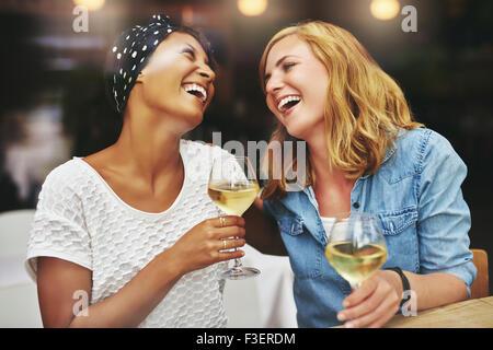 Due giovani attraenti vivace femmina multietnica amici celebrando e ridere insieme con un bicchiere di vino bianco Foto Stock