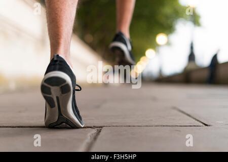 Giovane maschio corridori indossando dei formatori in esecuzione sul marciapiede Foto Stock