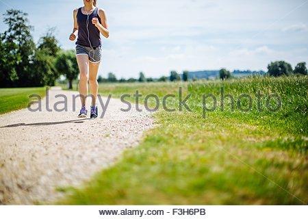 Giovane ragazza nel parco, in esecuzione sul percorso, sezione bassa Foto Stock