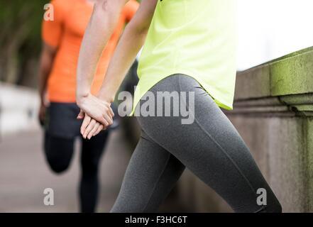 Giovane maschio e femmina guide città stretching gambe Foto Stock