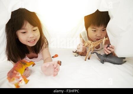 Giovani cinesi un ragazzo e una ragazza a letto a giocare con i loro giocattoli sotto le lenzuola Foto Stock