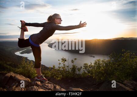 La donna a praticare yoga sulla collina, Angelo di riposo, Columbia River Gorge, Oregon, Stati Uniti d'America Foto Stock