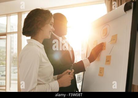 Due colleghi di lavoro lavorando sul progetto insieme. La gente di affari di mettere le loro idee sulla lavagna Foto Stock