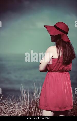 Giovane donna in un abito rosso sulla spiaggia Foto Stock