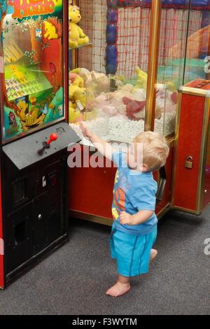 Bambino con macchina arcade in playbarn Foto Stock