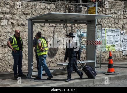 (151013) -- Gerusalemme, 13 ottobre, 2015 (Xinhua) -- Un ultra-ebrea ortodossa uomo cammina passato il sito di una stazione degli autobus attentato a Gerusalemme, su 13 Ottobre, 2015. Almeno tre israeliani sono stati uccisi e 26 altri feriti in quattro attacchi di palestinesi a Gerusalemme e la città di Ra'anana Martedì mattina la polizia israeliana detta. Un palestinese su un furgone con il logo di Israele nazionale di telecomunicazioni della società, Bezeq, correva su pendolari in corrispondenza di una stazione di autobus in Geula quartiere nel centro di Gerusalemme. Egli si è poi recato al di fuori del suo veicolo, che trafigge i passanti con un coltello. Servizi di salvataggio ha detto che ha ucciso uno e injur