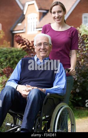 Figlia adulta spingendo il Padre in carrozzella Foto Stock