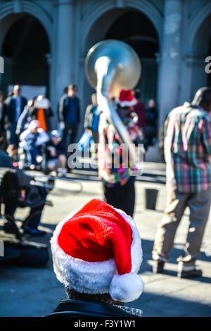 Vista posteriore dell'uomo indossa Santa hat intrattenimento da musicisti di strada, Jackson Square, il quartiere Foto Stock