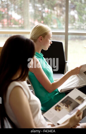 Lettura delle donne per uccidere il tempo nella sala d'attesa Foto Stock