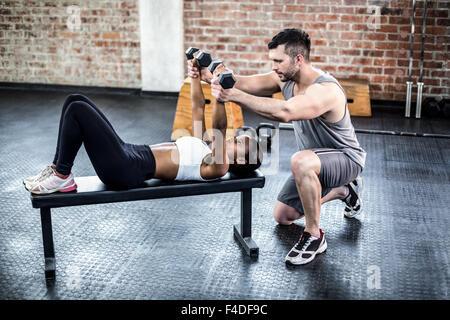 Personal trainer lavora con il cliente tenendo il manubrio Foto Stock