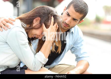 Vista laterale di un uomo musulmano consolante una triste ragazza caucasica lutto in una stazione ferroviaria Foto Stock