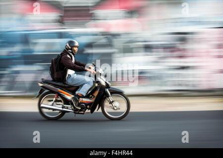 Il panning fotografia immagine del motociclista accelerando da una offuscata coperto di graffiti. parete effetti Foto Stock