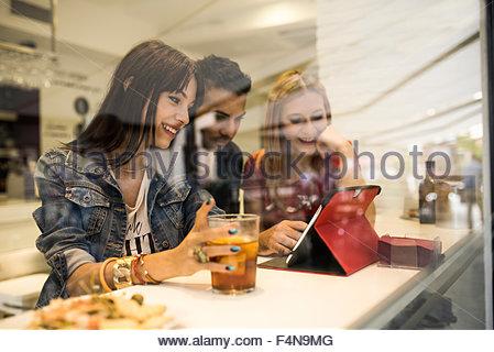 Tre amici in un bar con bevande con tavoletta digitale Foto Stock